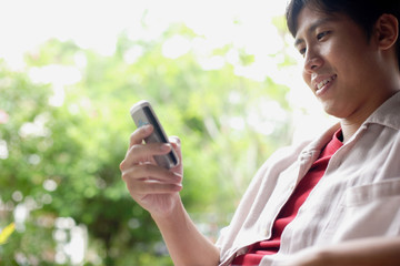 Man using mobile phone, text messaging, smiling