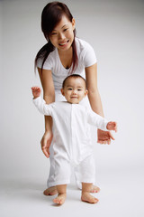 Baby girl standing, mother behind her, portrait