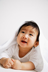 Baby boy peeking out from under blanket, portrait