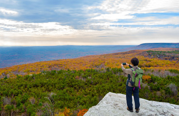 Mature asian woman hiking in autumn and taking picture of the view