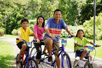 Family on bicycles, looking at camera