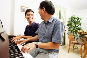 Father and son playing piano, sitting side by side