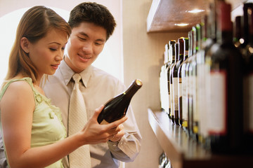 Couple reading label on wine bottle
