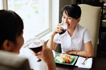 Two women at restaurant, sitting face to face, drinking wine, food on the table