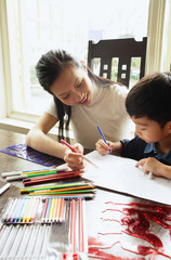Mother sitting with son, drawing with colour pencils