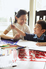 Mother sitting with son, colour pencils and drawing paper on the table, son holding pencil, looking up