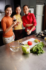 Women in kitchen, smiling at camera