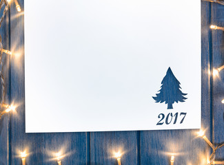 Cut paper in fir-tree shape with decorative lights for christmas card or new year background on blue wooden table