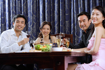 Couples having dinner at home, smiling at camera