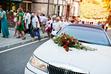 Elegant white limousine with a bouquet of flowers on the hood, background guests on wedding