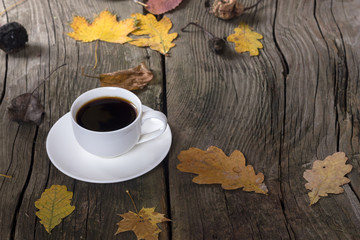 white cup of coffee on a wooden background with autumn leaves