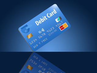 A debit card in blue is seen on a dramatic blue background on a reflective tabletop. This is a photo illustration combining photographs with artwork and is free of copyright. Cards are generic and saf