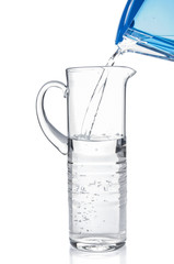 Pouring clear water from filter pitcher in glass jug on white ba