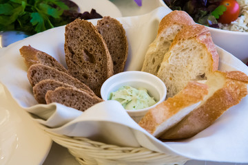 White bread and black bread with greens. Sliced bread on the serving table in a wicker basket with white sauce. The food for Breakfast, lunch and dinner.