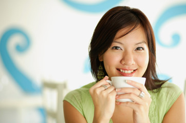 Woman holding cup, smiling at camera