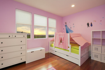 Beautiful girls room in bright pink color with furniture, bed and toys.