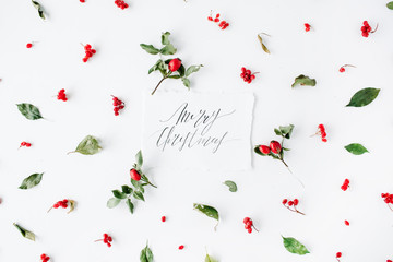 words merry christmas and minimal creative berry arrangement pattern on white. flat lay, top view. christmas background wallpaper.