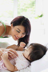 Baby girl lying on bed, mother leaning over her