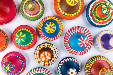 Top view of colorful painted handmade pottery lids on white background