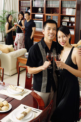 Couple at home, holding wine glasses, smiling at camera, people in the background