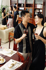 Couple in dining room, holding wine glasses, people in the background