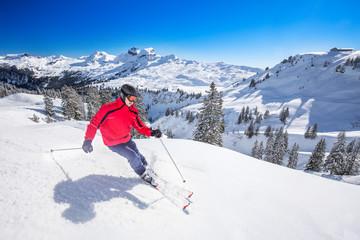 Wall Mural - Young man skiing in Hoch-Ybrig ski resort, Swiss Alps