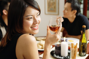 Woman with wine glass, looking away, smiling