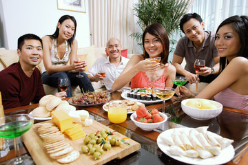 Adults having a party in living room, smiling at camera, food on coffee table