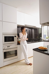 Young woman standing in kitchen, having coffee