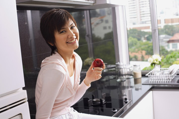 Young woman sitting on kitchen counter, holding an apple