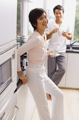 Couple standing in kitchen, having coffee, looking at camera