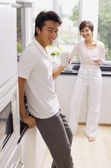 Couple in kitchen, having coffee, smiling at camera