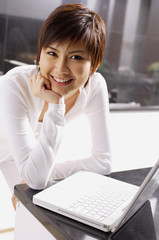 Young woman leaning on kitchen counter, hand on chin, laptop open in front of her