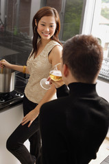 Couple in kitchen, woman cooking at stove, man drinking wine glass
