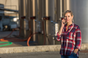female worker speaking on mobile phone in an industrial area