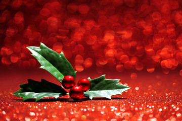 Sprig of holly red glitter background