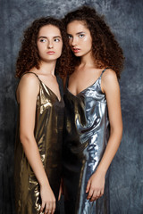Young beautiful sisters twins posing over grey background.