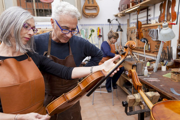 group of mature violin maker in pose while testing the violins i
