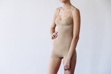 Beautiful mixed race caucasian woman posing in beige underwear like mannequin for sale isolated in white.