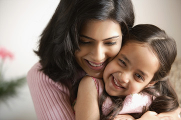 close up of mother hugging daughter, girl is smiling at camera