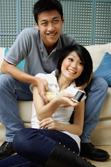 Couple in living room, woman holding remote control