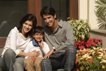 father, mother, son smile for camera on front doorstep