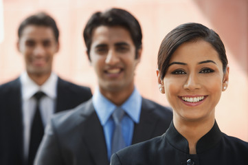 smiling businesswoman, two businessman in background