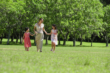Mother and two daughters holding hands, walking across park
