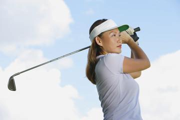 Woman wearing sun visor, swinging golf club
