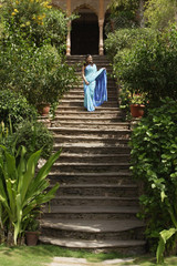 young woman in sari, standing on stairs