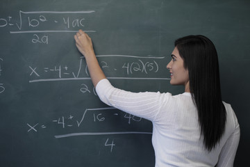 Rear view of young woman writing math equation on chalk board