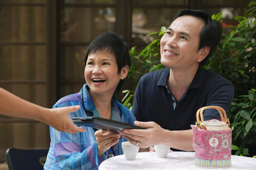 Mature couple being handed menu in restaurant