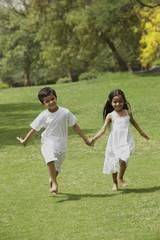 two little children running through a park holding hands