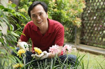 Man gardening and smiling at camera